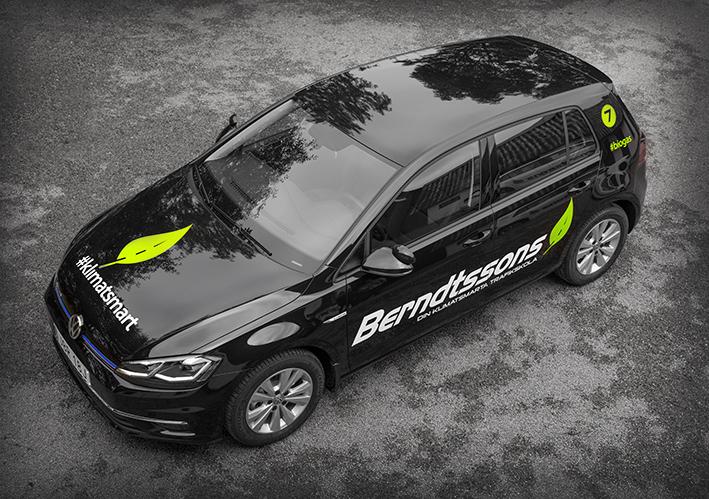 En svart bil fotograferad snett ovanifrån. På motorhuven syns Berndtssons Trafikskolas symbol, ett grönt löv och hasttaggen klimatsmart. På sidan av bilen syns Berndtssons Trafikskolas logotyp.