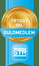 STR logotyp i guld på blå bakgrund. Det står tryggt val och guldmedlem skrivet på logotypen.